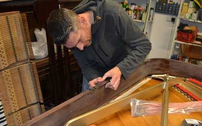 Jo, the polisher mending a dent on the side of a Chappell Grand piano
